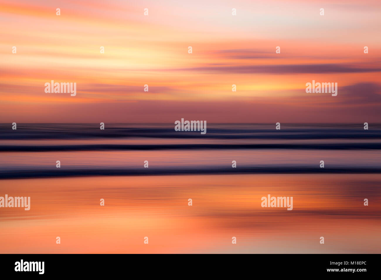 Motion blur of ocean and waves with a colourful sunrise. - Stock Image