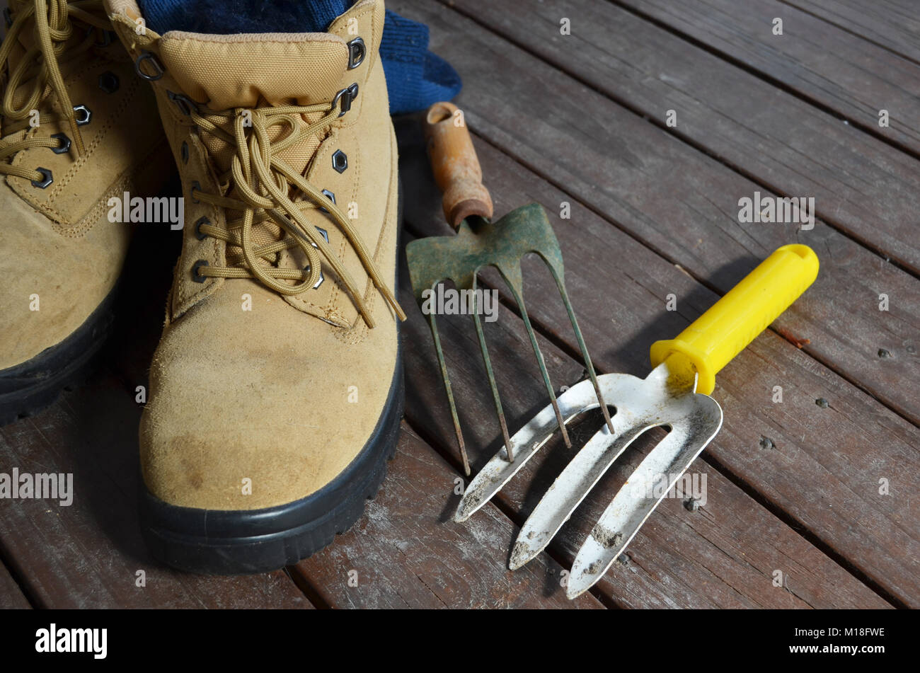 Pair of work boots with garden tools on a wooden deck Stock Photo
