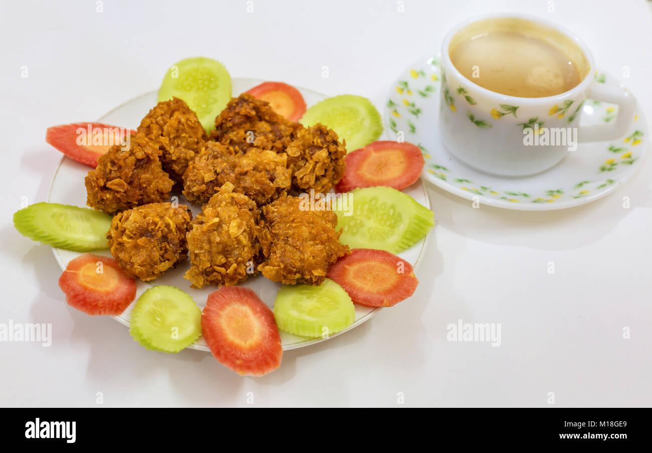Crispy deep fried chicken pakora garnished with sliced carrots and cucumber served as snacks with tea. A popular - Stock Image