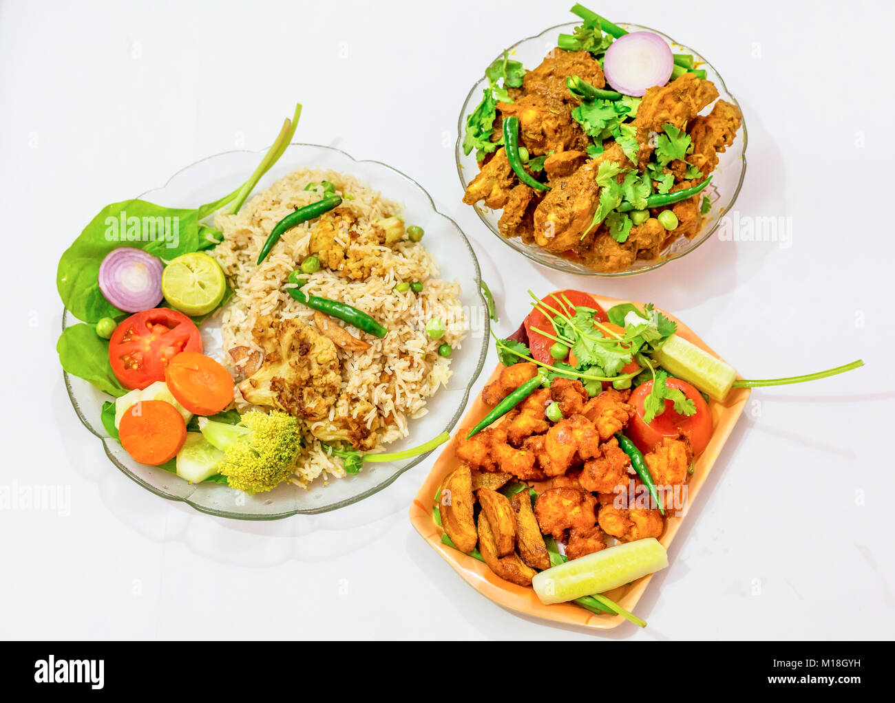 Indian cuisine dishes veg fried rice and spicy chicken kosha isolated on white background. A popular Bengali food. - Stock Image