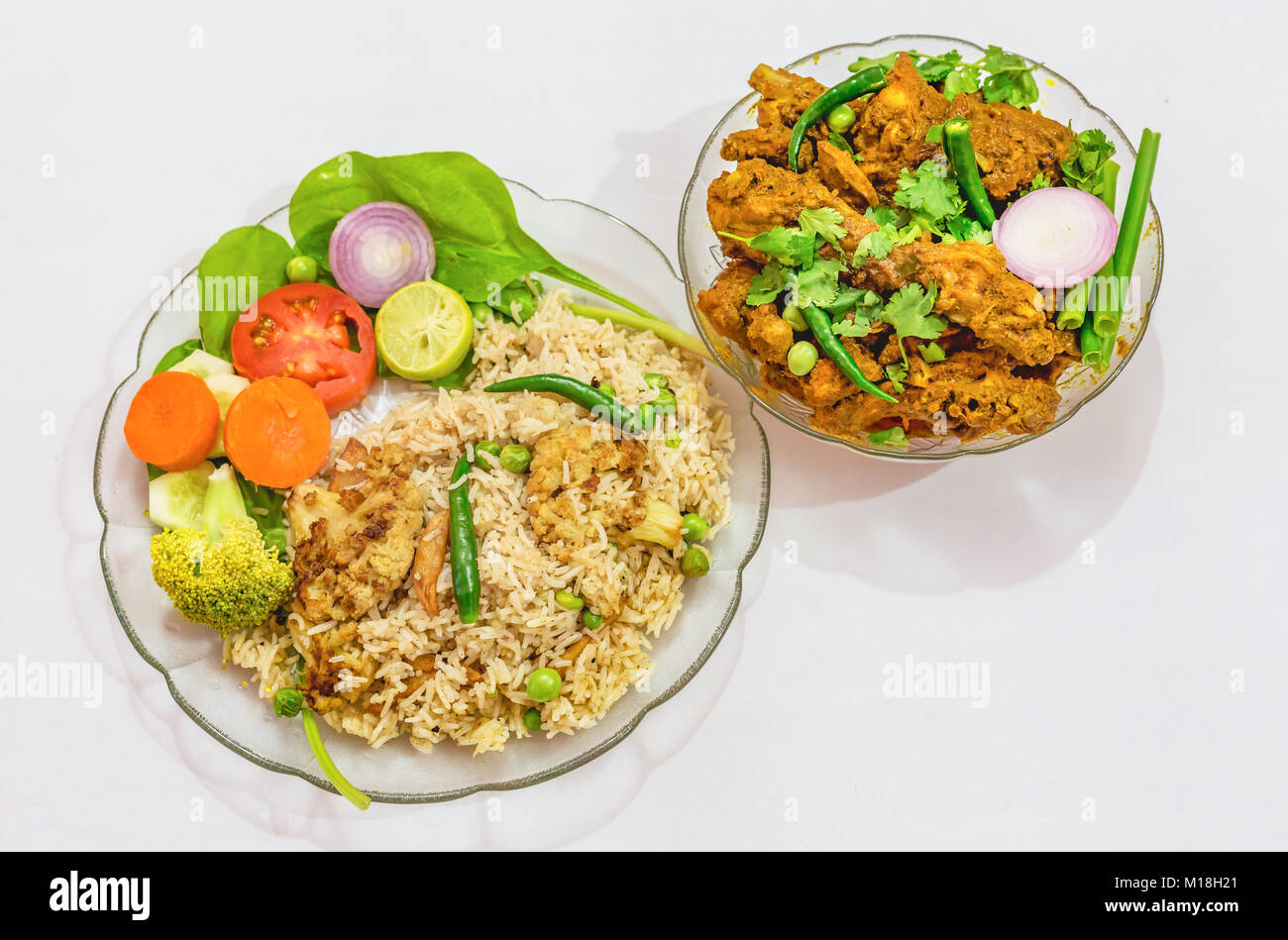 Indian meal of veg fried rice and spicy chicken kosha isolated on white background. A popular Bengali food. - Stock Image
