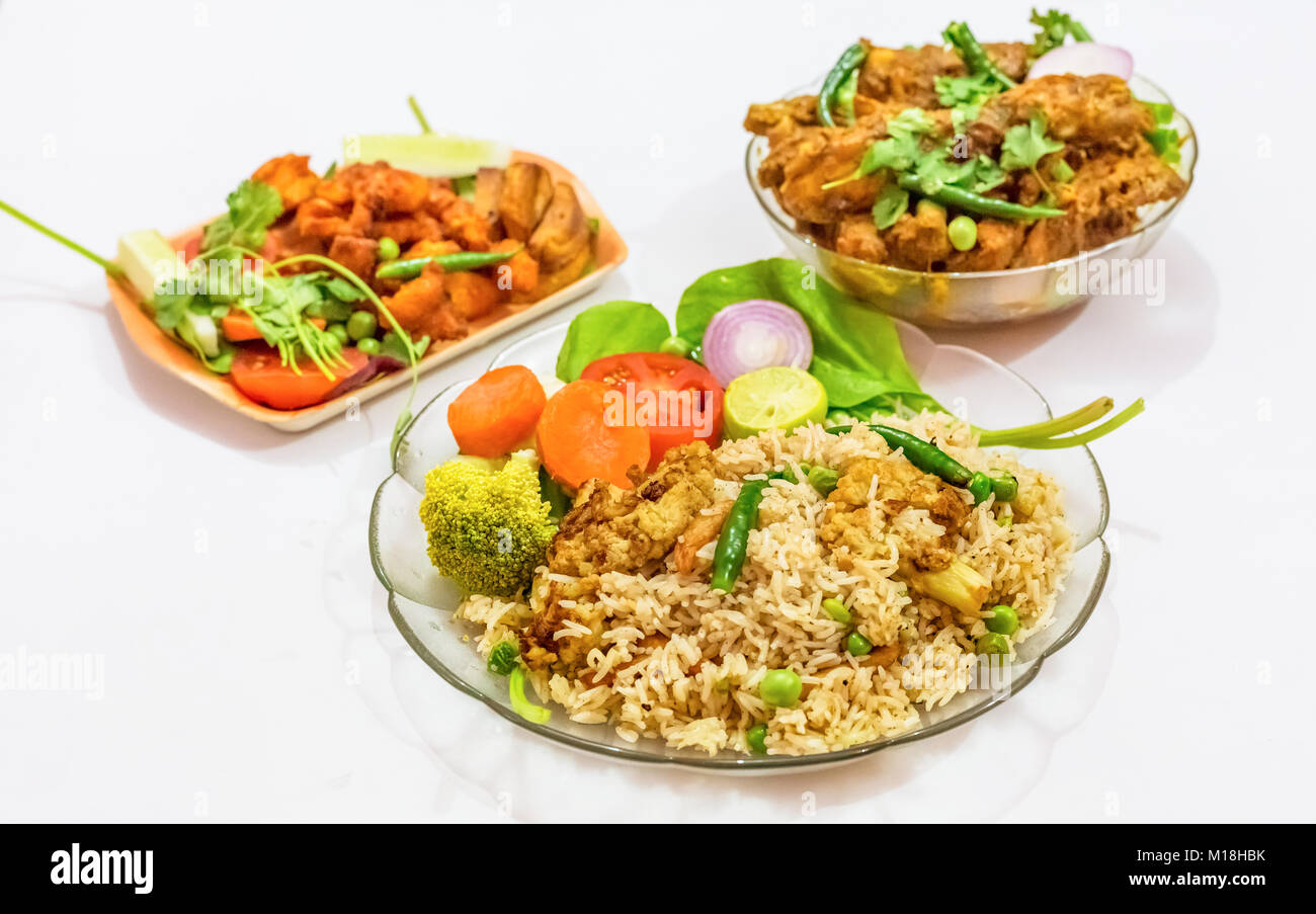Spicy Bengali Indian dish of vegetable fried rice with chicken kosha as side dish and crispy chicken prawn as starter - Stock Image