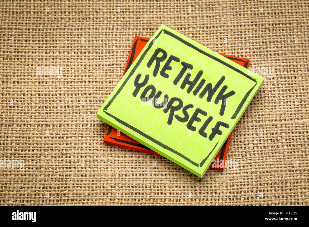 rethink yourself advice or reminder  - handwriting on a sticky note against burlap canvas - Stock Image