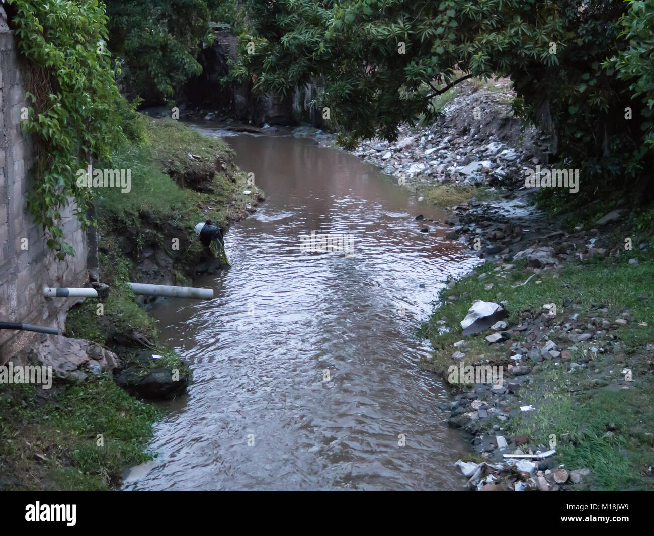 Holguin, Cuba - August 31, 2017: Slow muddy stream with visible trash seen on the sides. Stock Photo