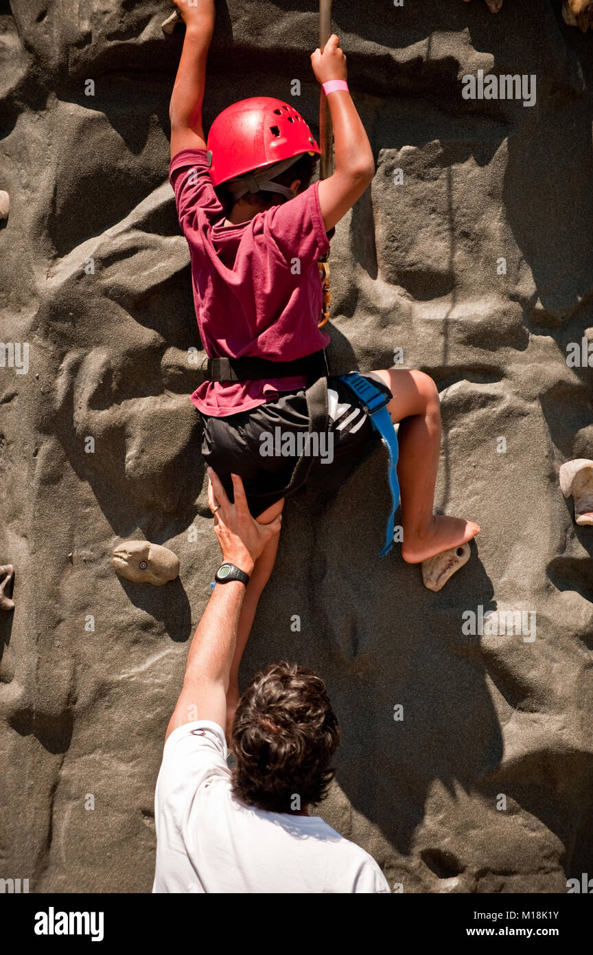 A father pushes his on up on rock climbing Stock Photo