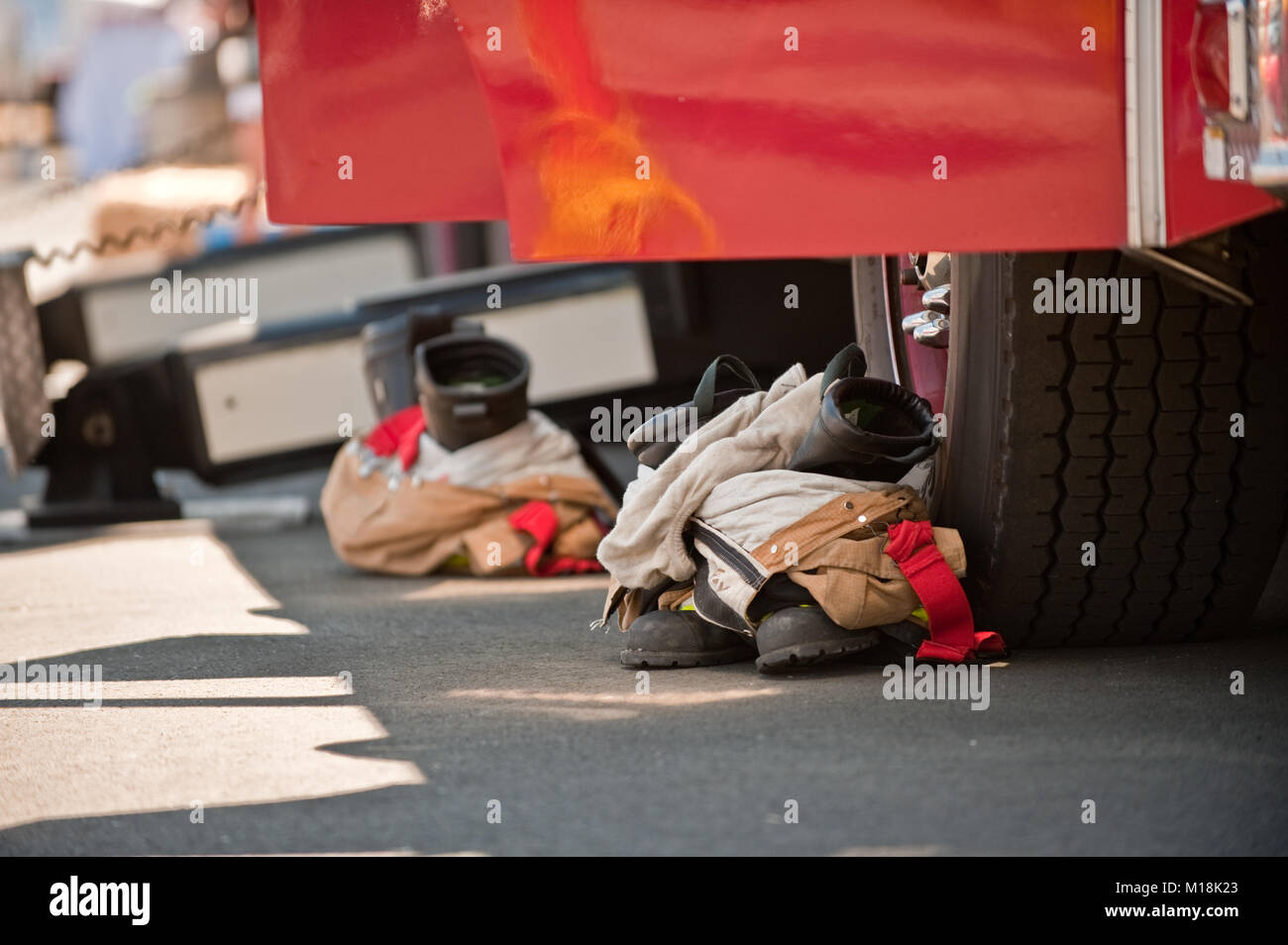 Close up view of pairs of fire boots and fire pants outside a fire truck at a public event - Stock Image