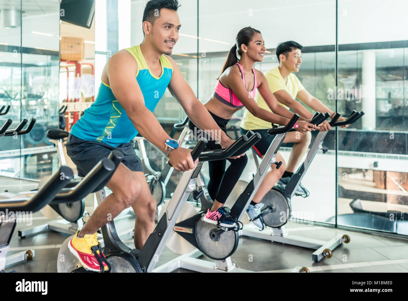 handsome and confident young man during group class of HIIT indo - Stock Image