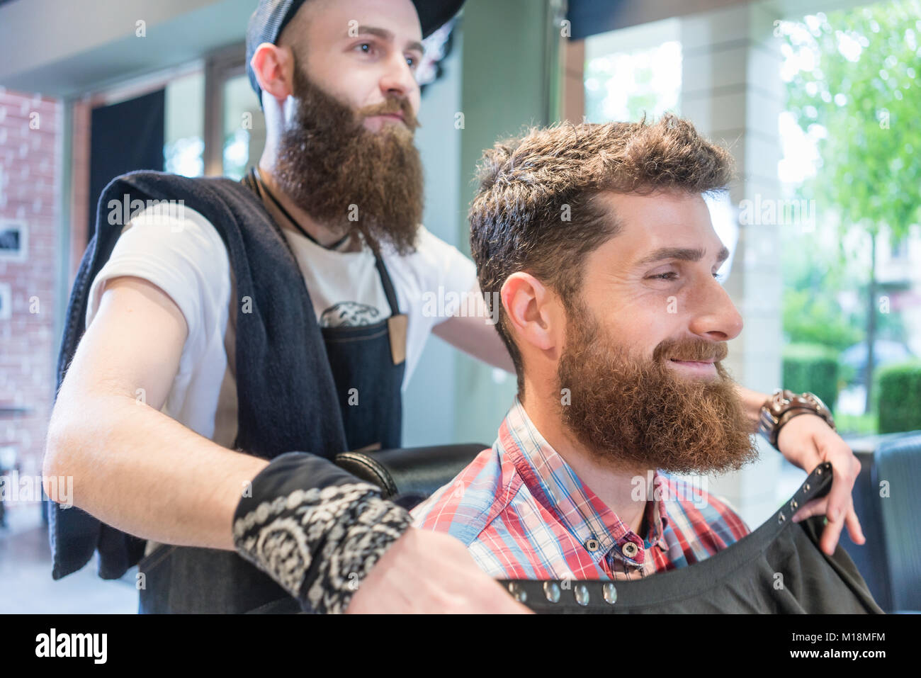 Handsome young bearded man smiling before having a trendy haircu - Stock Image