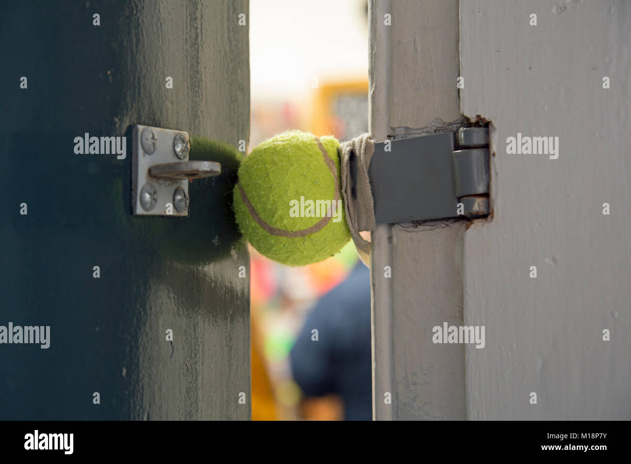 A close up of a tennis ball being used to stop a door banging shut - Stock Image