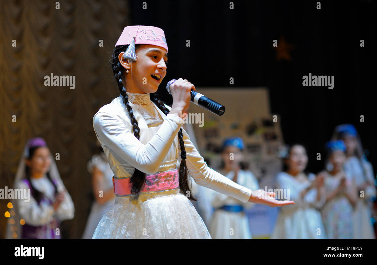 Crimean tatar baby girl in native dress performing native song on stage. Celebrating nowruz (Turkic New Year). December - Stock Image