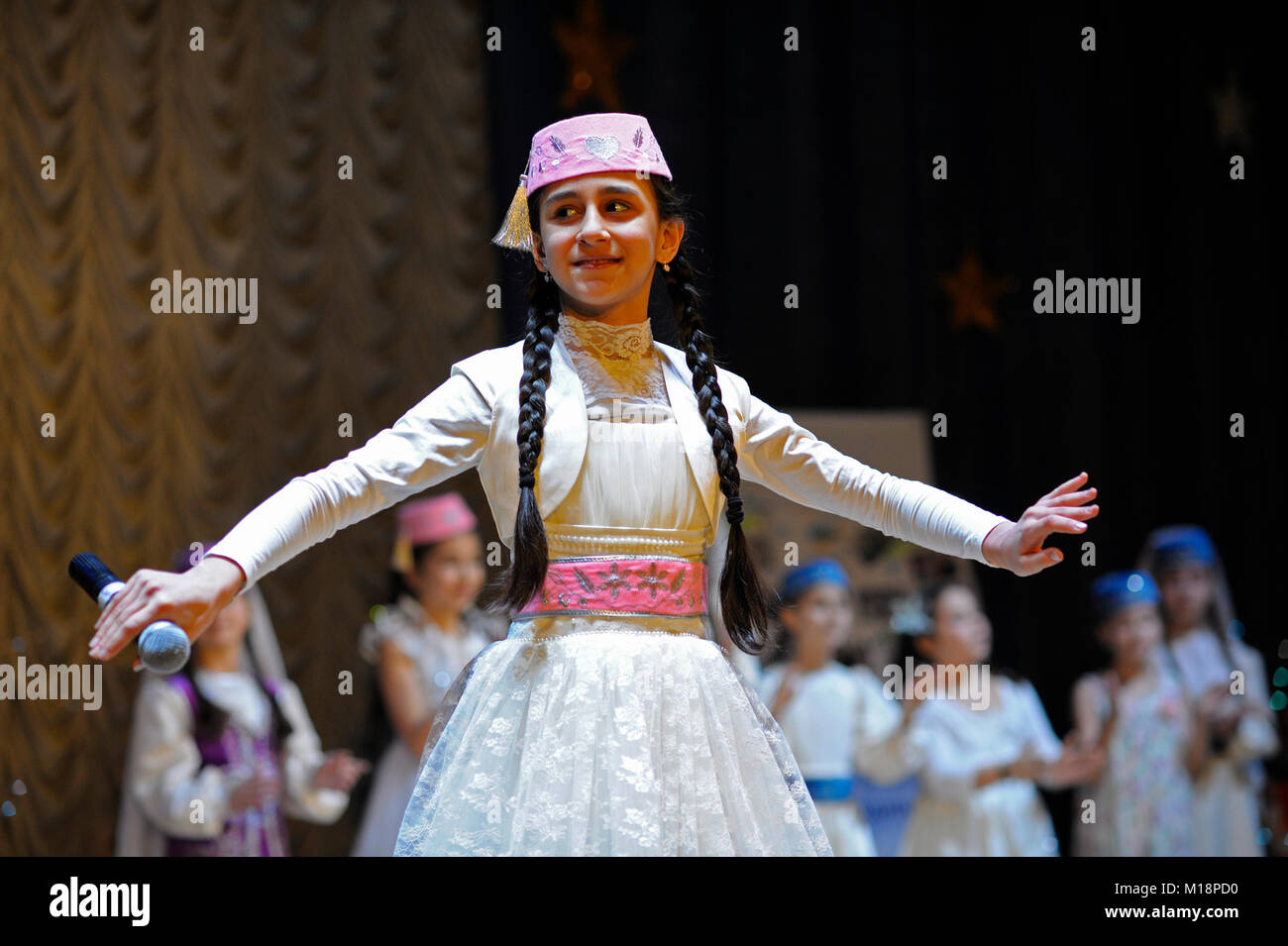 "Crimean tatar baby girl in native dress performing native song on stage. Concert ""Winter tale"". December 24, 2017. - Stock Image"