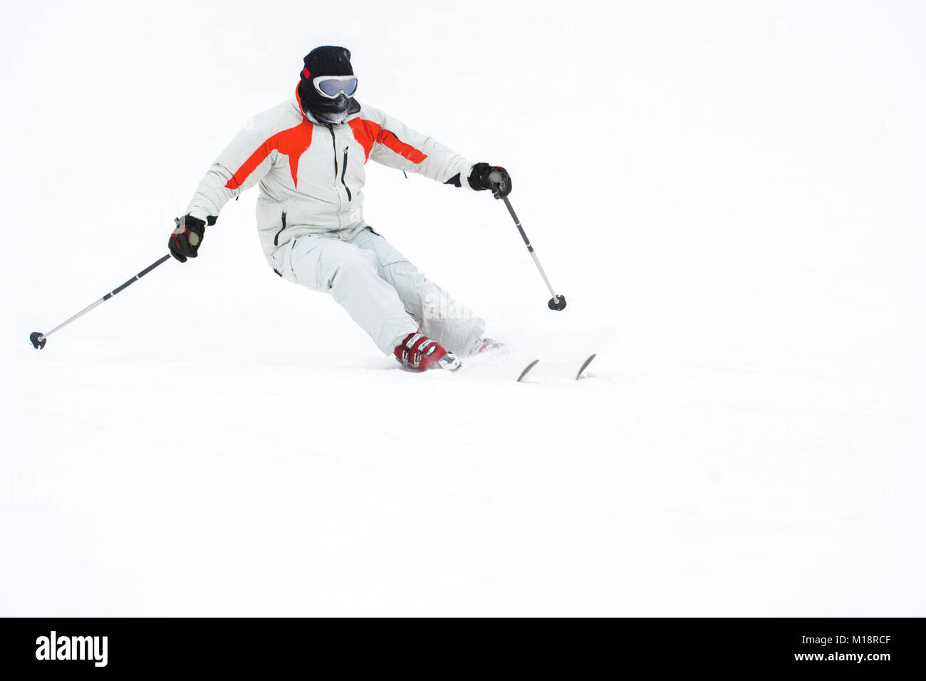 Alpine skier skiing downhill over white snow background - Stock Image