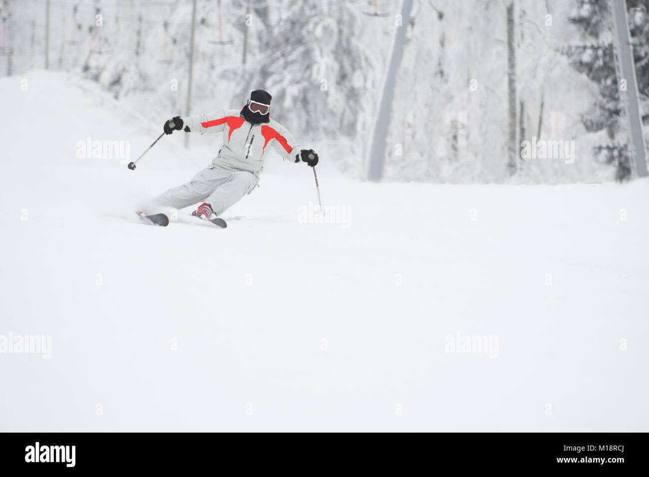 Alpine skier skiing downhill over white snow background - Stock Image