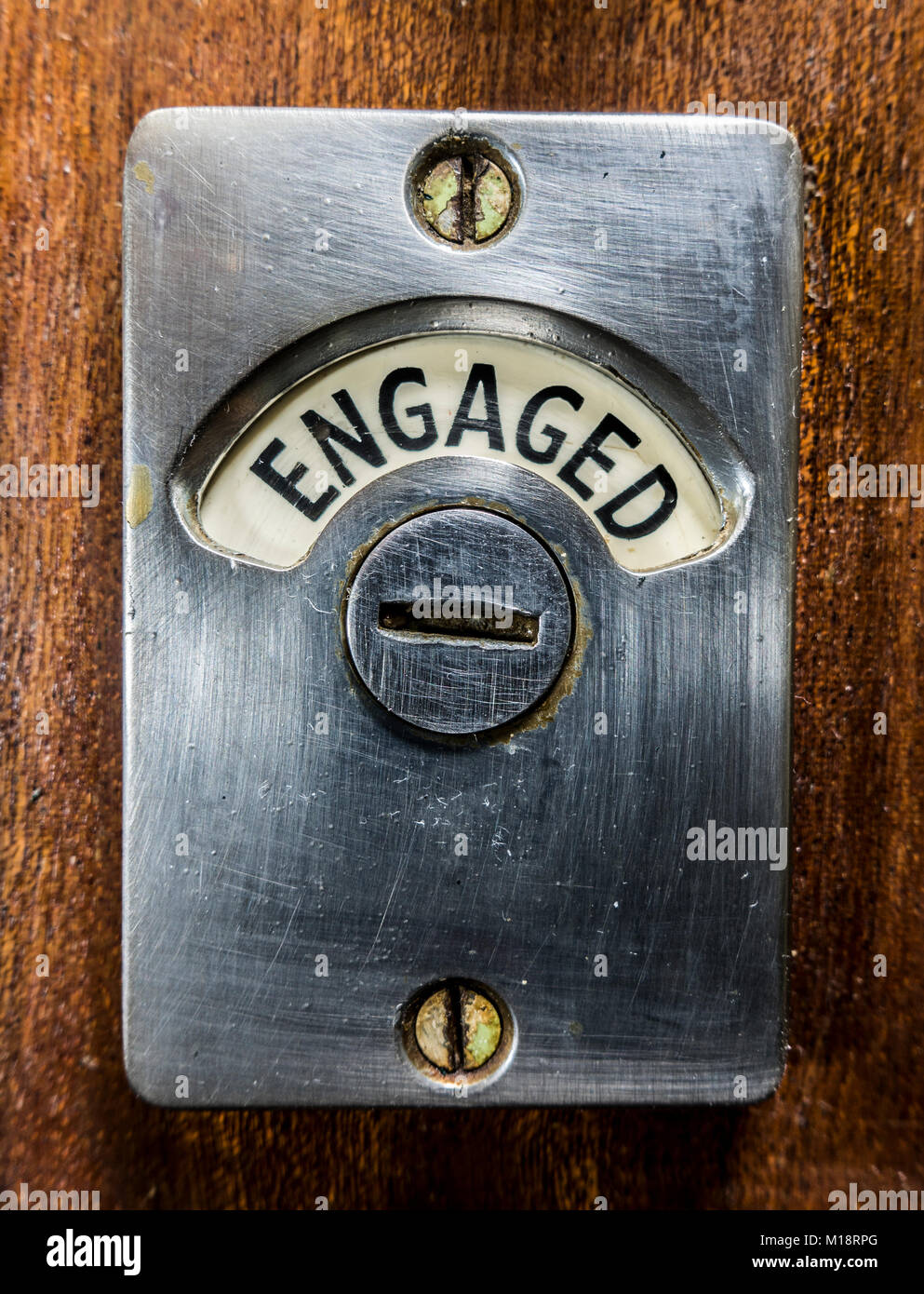 Traditional old metal 'engaged' sign / notice screwed to a locked wooden door, to show other users that a toilet - Stock Image