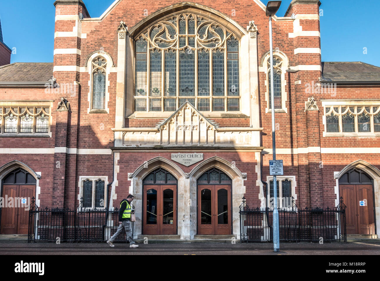 Man walking past the historic Baptist Church (Christian faith) in Park Road, Peterborough city centre, Cambridgeshire, - Stock Image