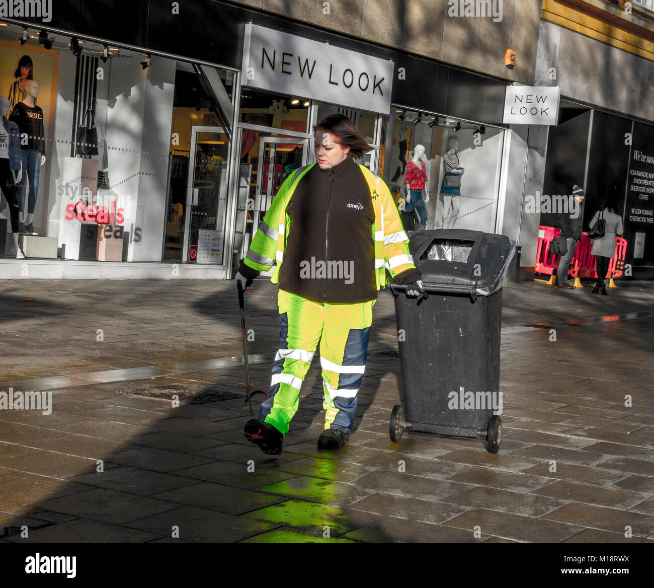 Young woman / female refuse and waste collector / street cleaner, wearing fluorescent clothing. Peterborough city - Stock Image