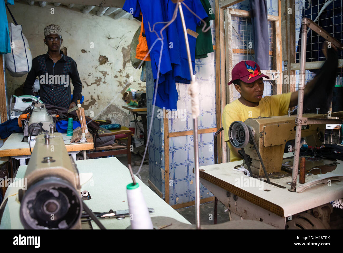STONE TOWN, ZANZIBAR - DEC 31, 2017: Tailor men sewing garments with industrial machines in workshop, Stone Town, - Stock Image