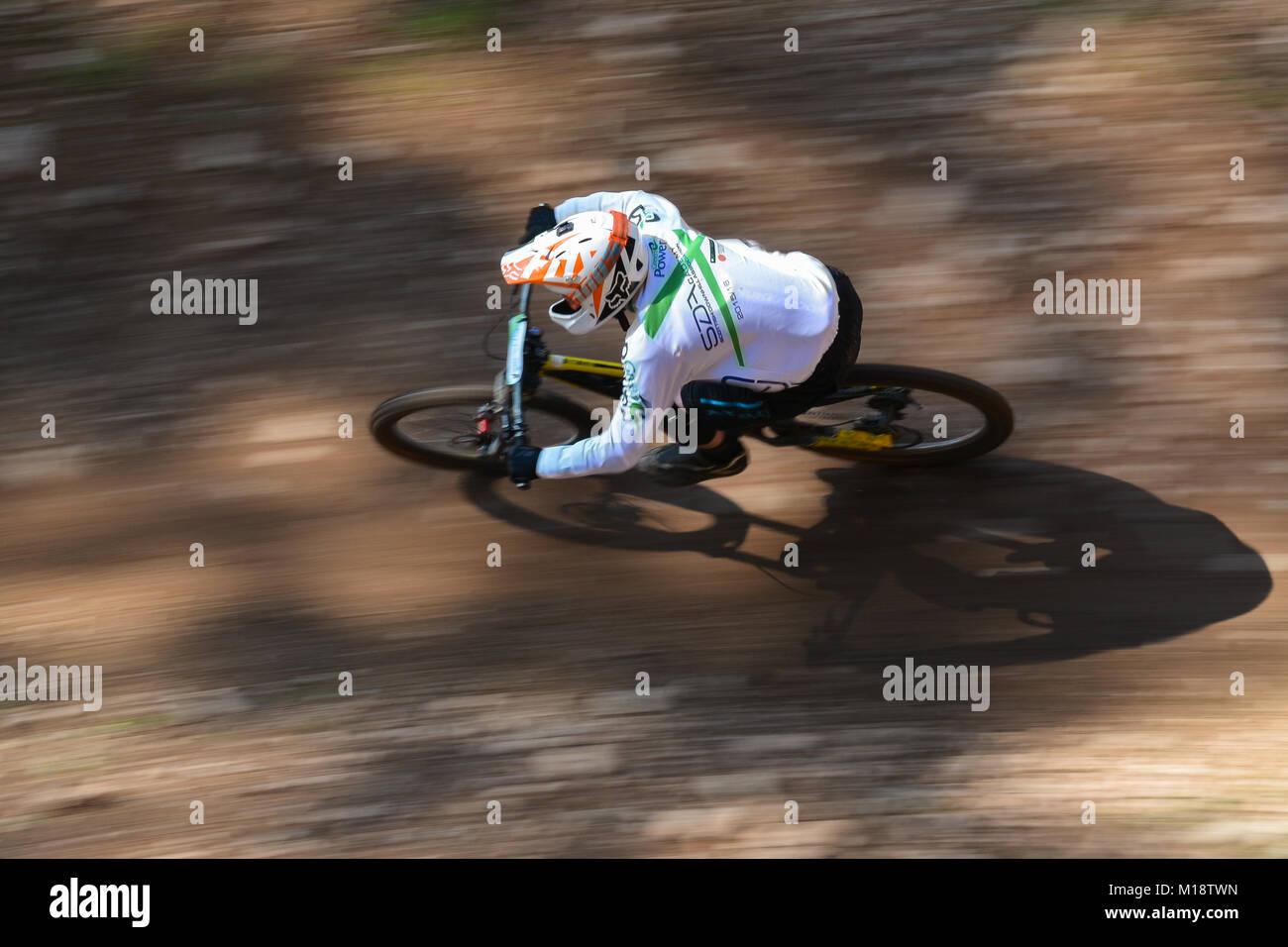 Downhill mountain biker with SDA Academy shirt - Stock Image