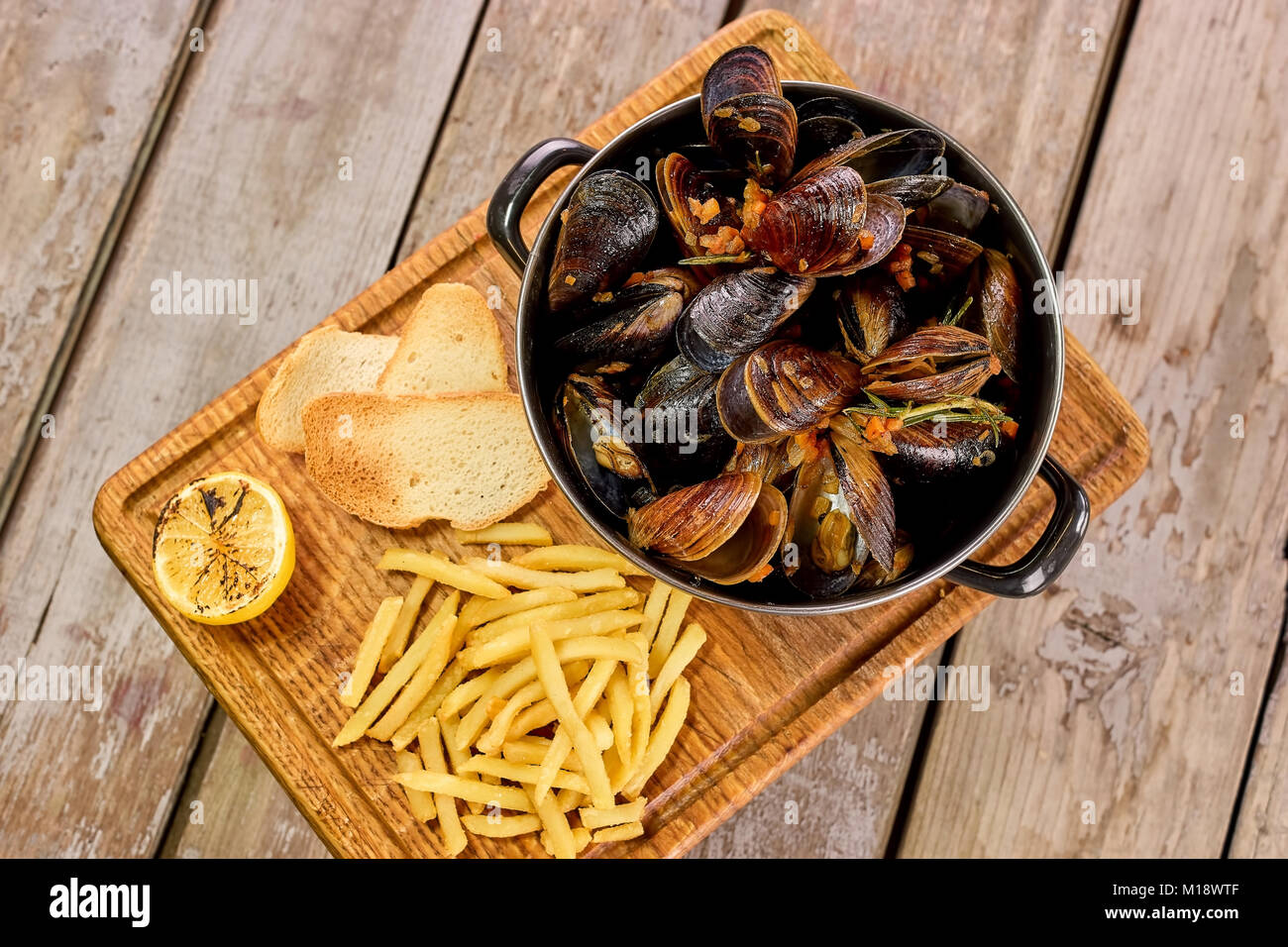 Many mussels in saucepan and side dish. Stock Photo