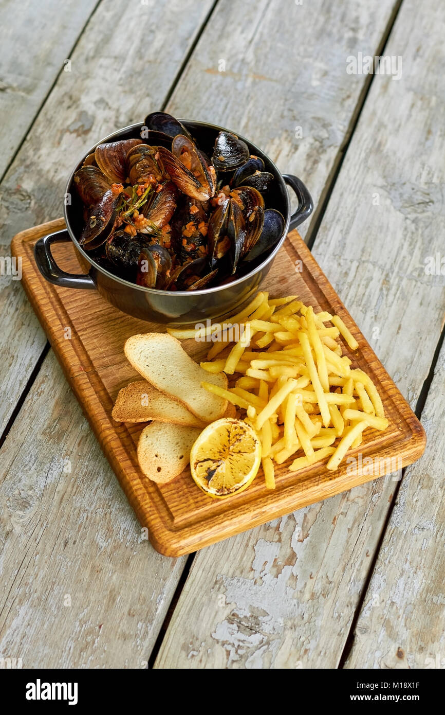 Top view saucepan with mussels and side dish. - Stock Image
