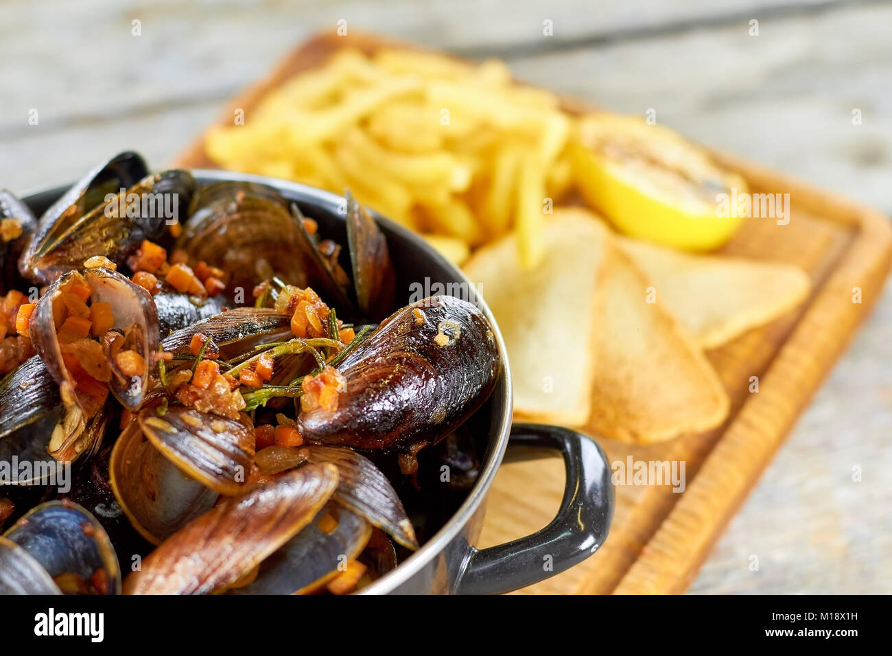 Close up saucepan with shell mussels and chopped vegetables. - Stock Image