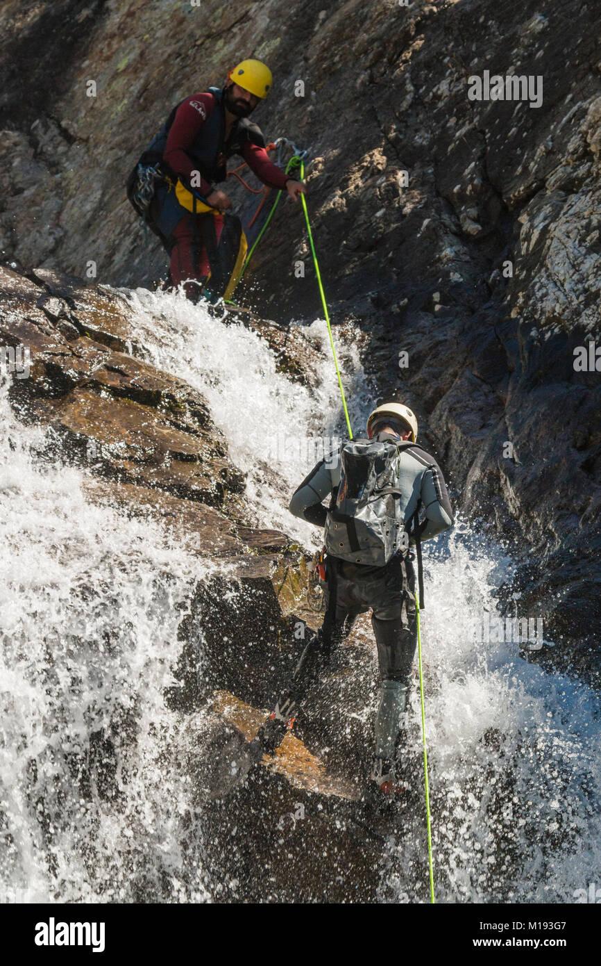 Men in wetsuits abseiling the Salto de Pino waterfall, by the Rio Caldares trail from Banos de Panticosa. Panticosa; Stock Photo