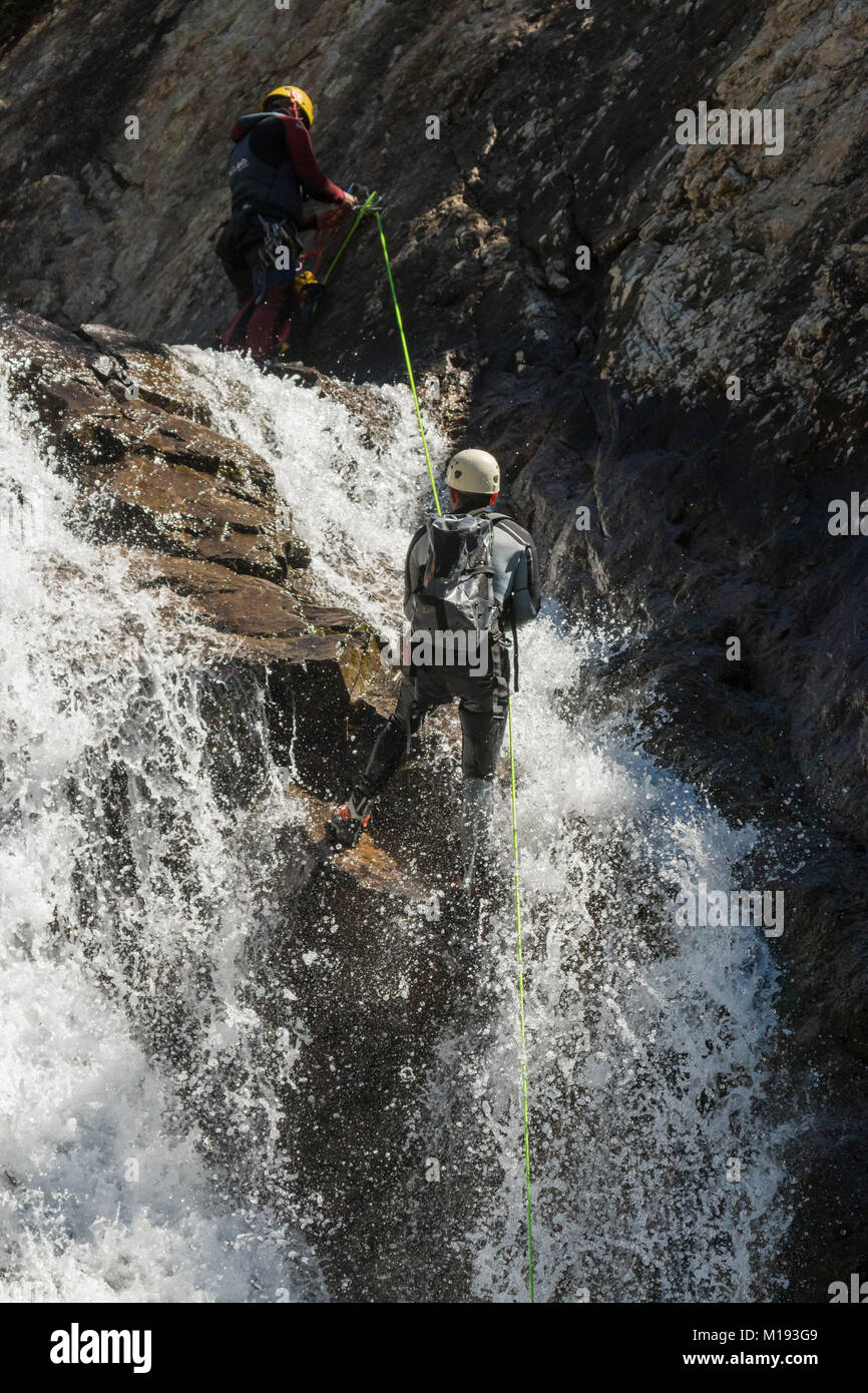 Men in wetsuits abseiling the Salto de Pino waterfall, by the Rio Caldares trail from Banos de Panticosa. Panticosa; Stock Photo