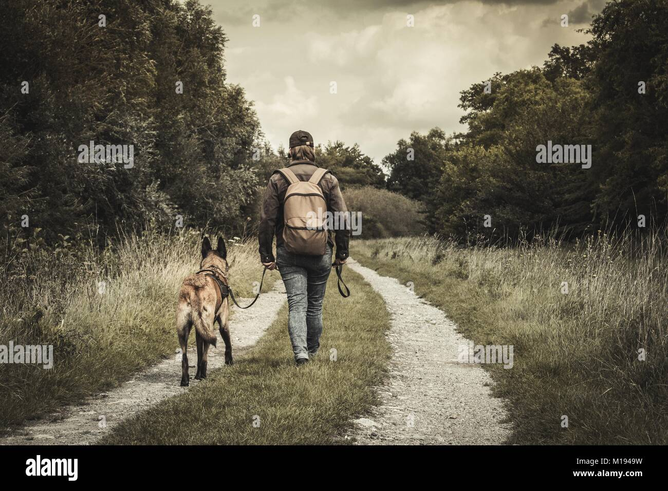 woman and her dog looking for houses. the discovery of abandoned buildings. post apocalypse. Stock Photo
