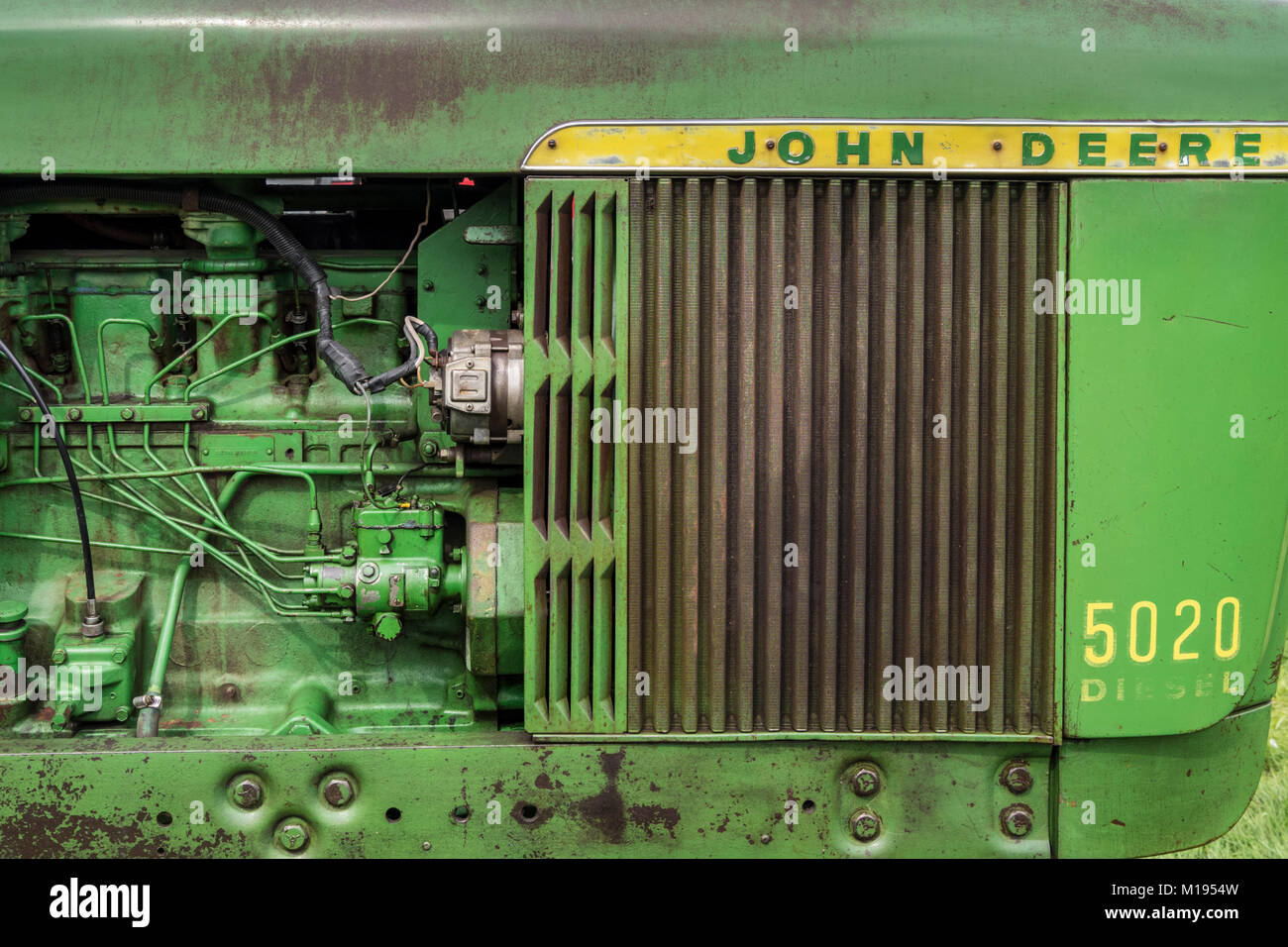 Side view detail of a vintage John Deere tractor, faded and worn green paint with yellow and green badge. - Stock Image