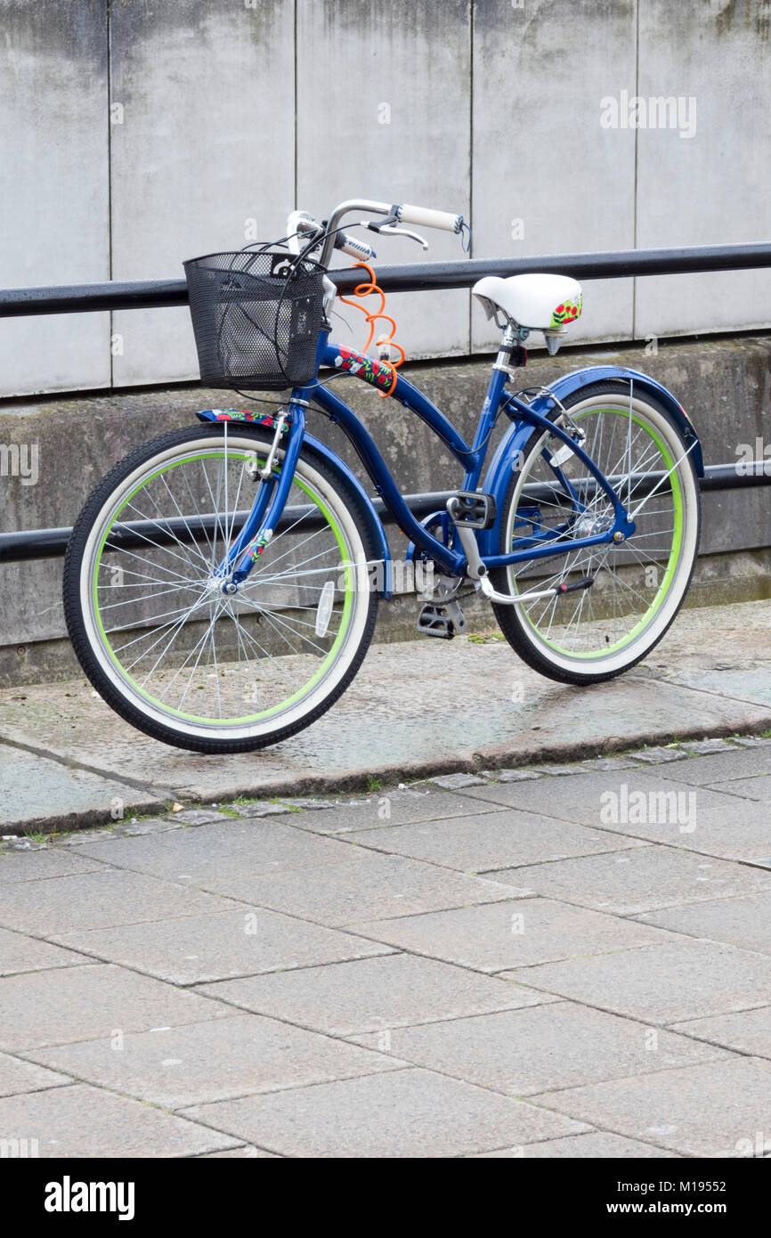 Blue Lady's or woman's bike with basket on the handlebars, leaning against and locked to railings - Stock Image