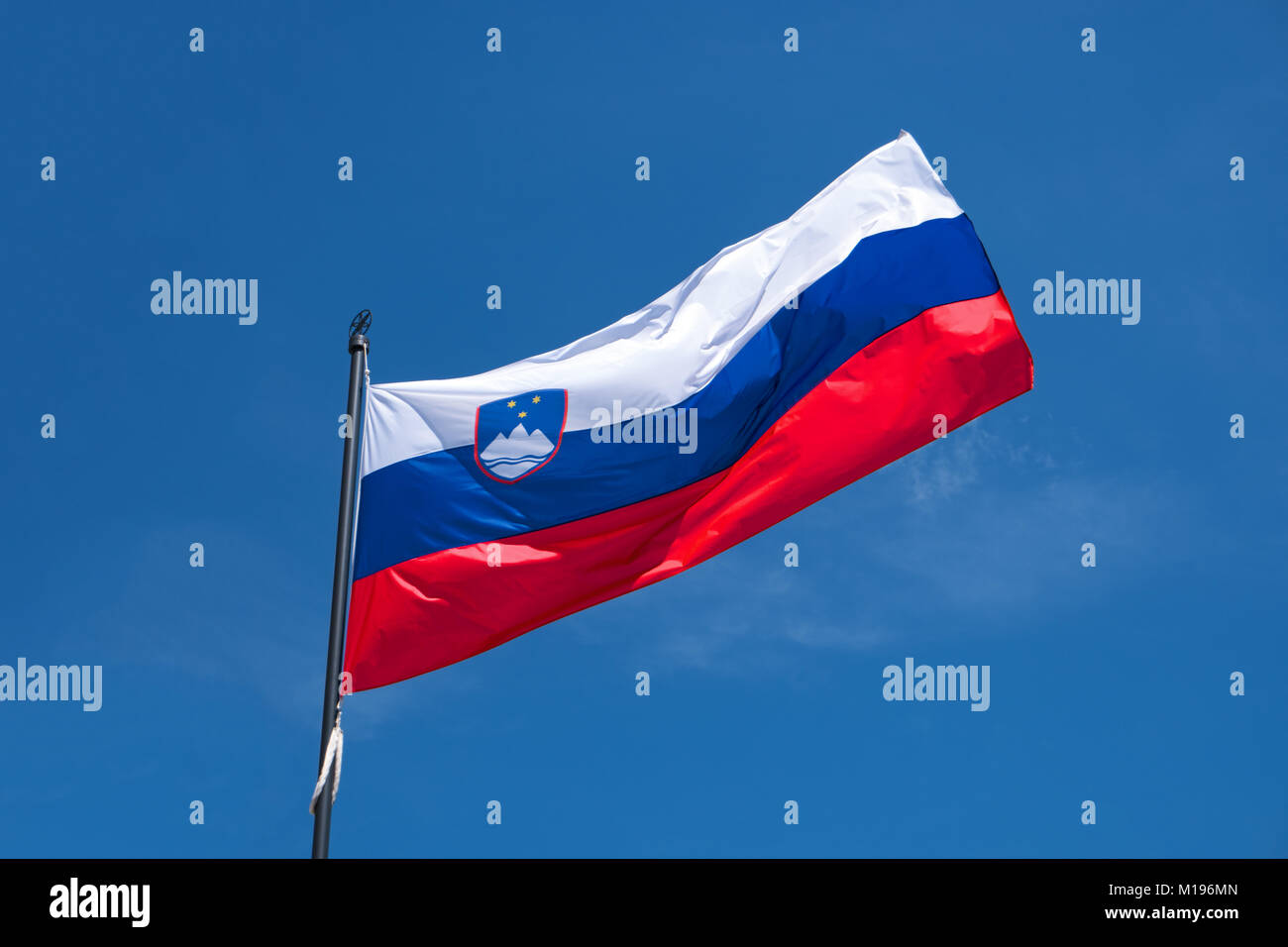 Flag of Slovenia on flagpole waving in the wind. Slovenian national official flag on blue sky background. Patriotic Stock Photo