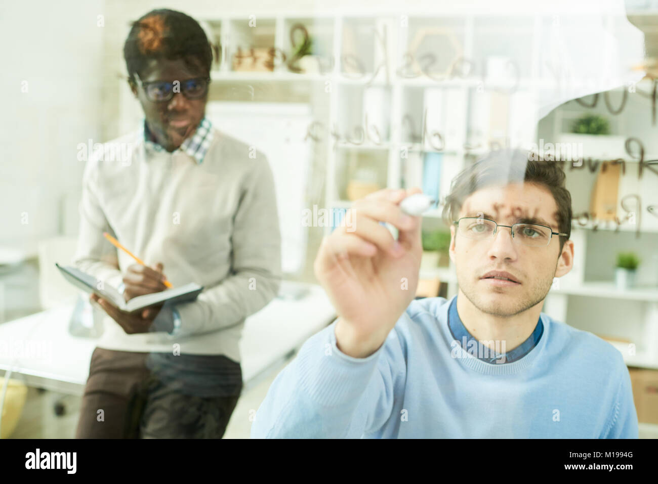 IT Developers Writing on Glass Wall - Stock Image