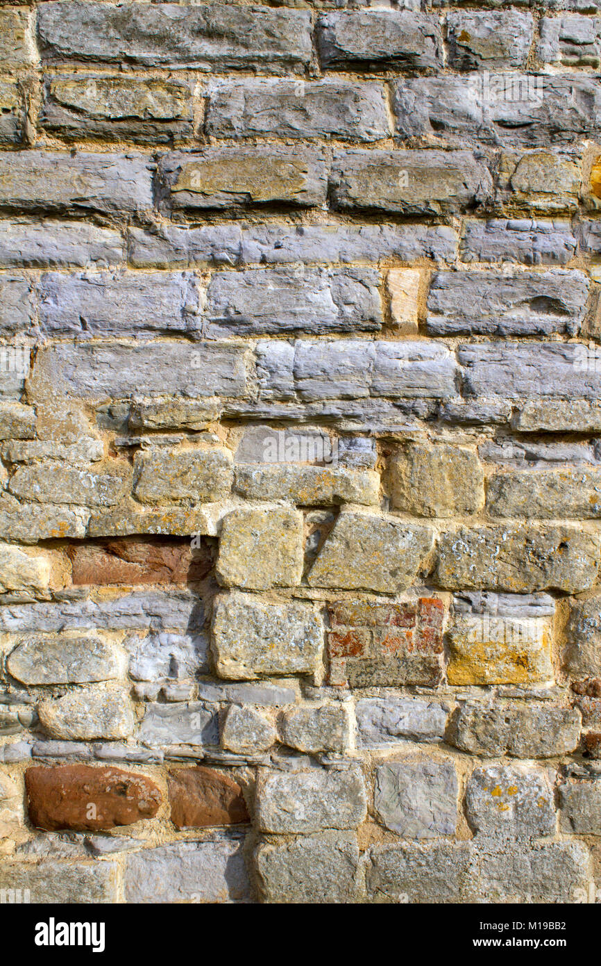 Stone and brick texture on an old worn and repaired wall, Tewkesbury, Gloucestershire, Severn Vale, UK - Stock Image