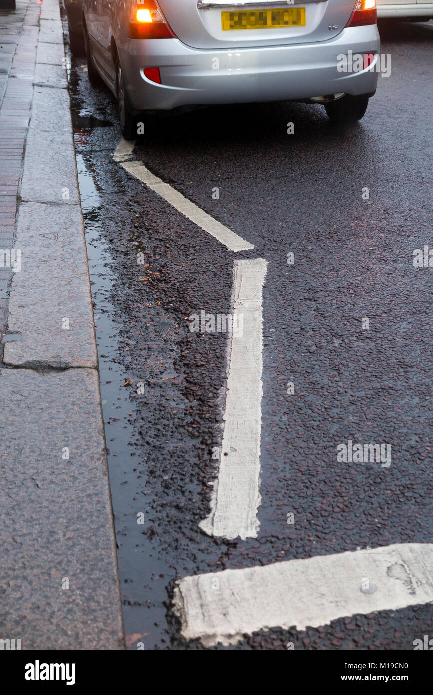 Illegally parked car waiting on zig zag white lines near a pedestrian pelican / toucan crossing. The penalty would - Stock Image
