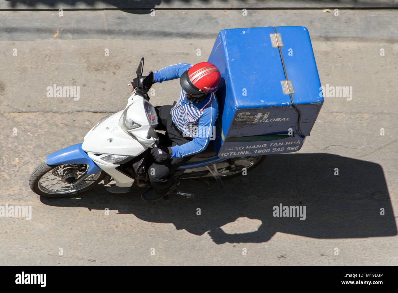 SAIGON, VIETNAM, DEC 17 2017, Delivery of consignments on motorbike. Motorcyclist rides with delivery in the large - Stock Image