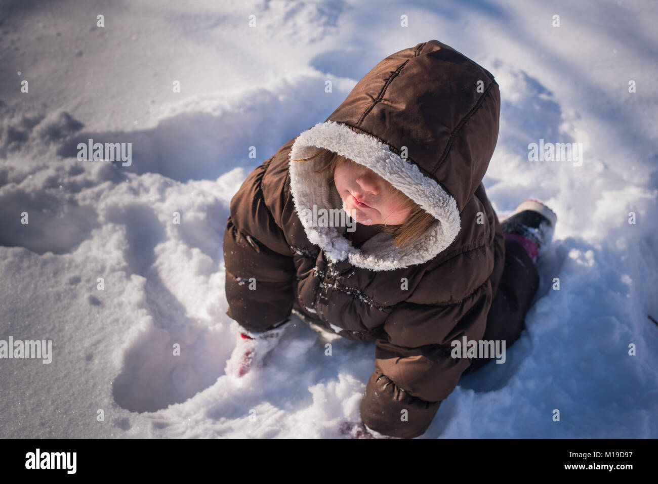 Looking down at a 3-year old toddler girl wearing a winter coat and sitting in the snow. - Stock Image