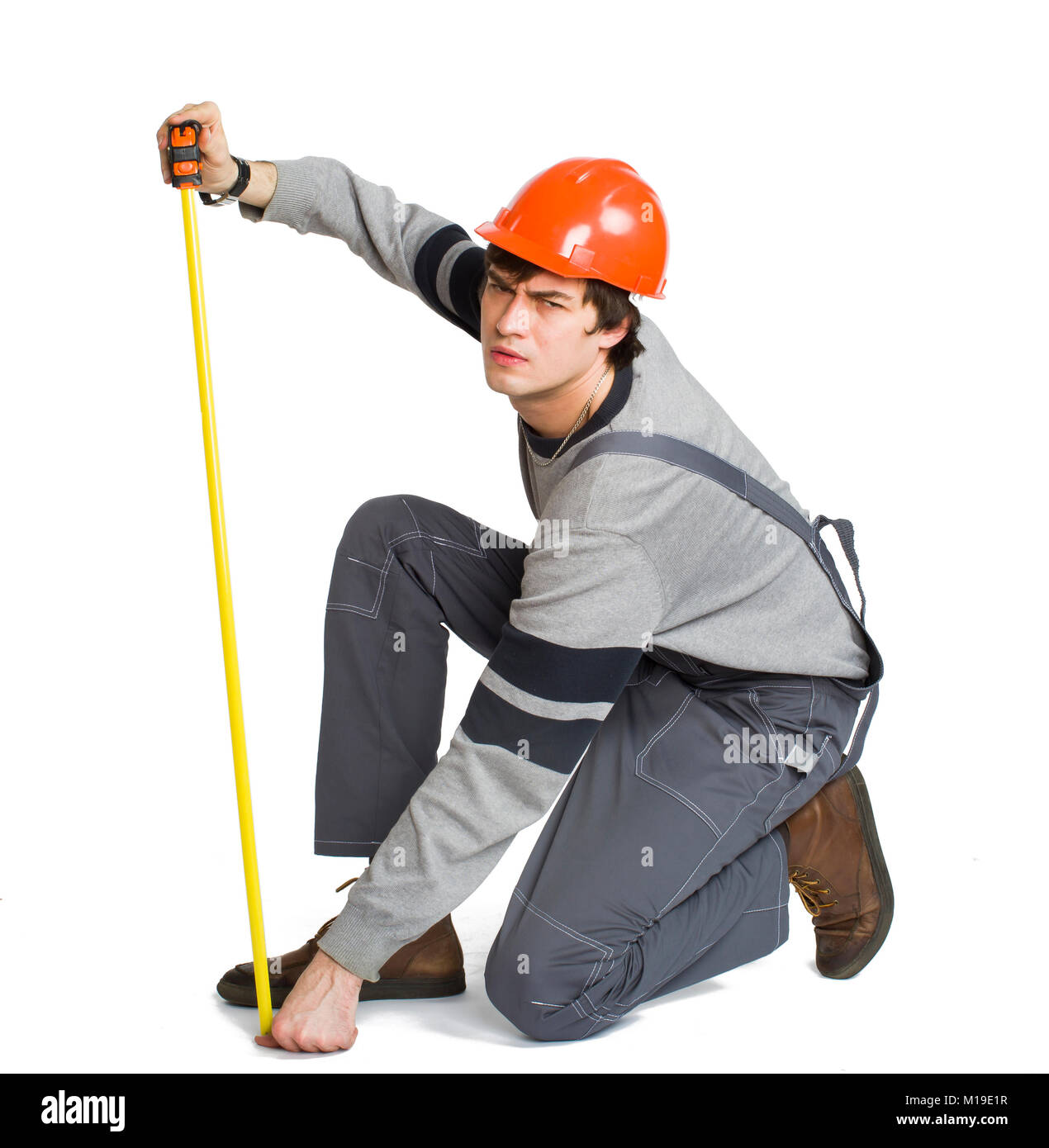 A young man in working grey clothes and orange hard helmet measuring the metric area in the room. - Stock Image