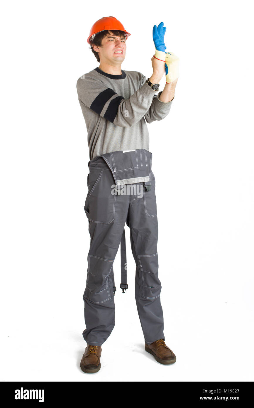 A young man in working grey clothes and orange hard helmet putting on a glove on white isolated background. - Stock Image