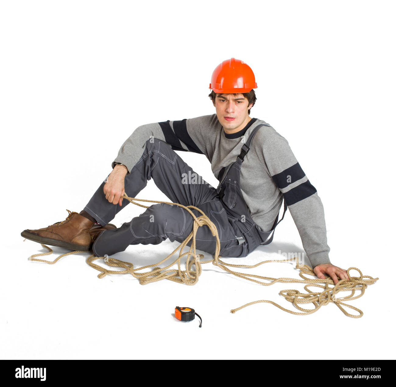 A young worker in grey uniform tied up with rope on white isolated background. Stock Photo