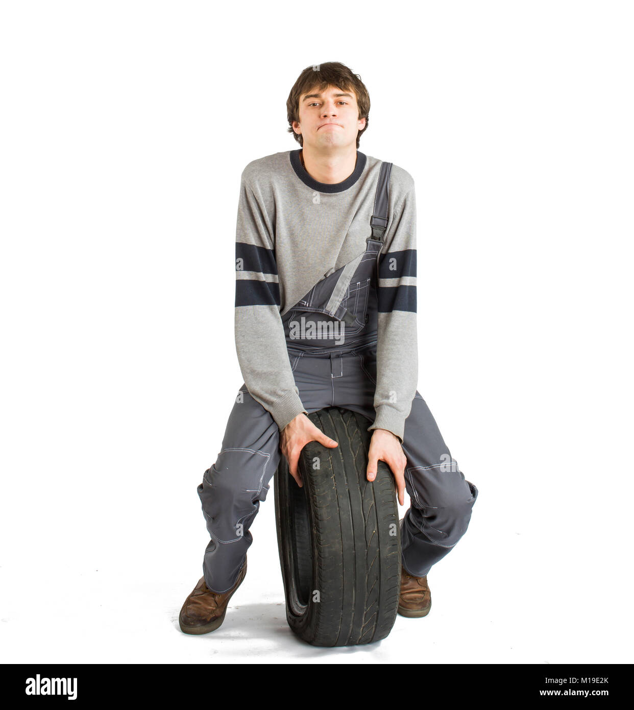 A young brunet foreman in working grey uniform with black wheel. - Stock Image