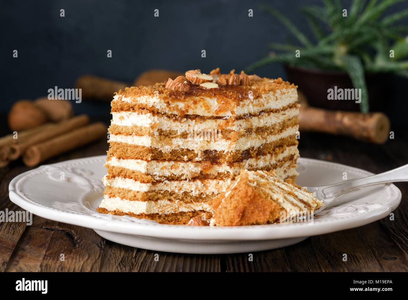 Honey cake with almonds on white plate. Russian cake Medovik - Stock Image