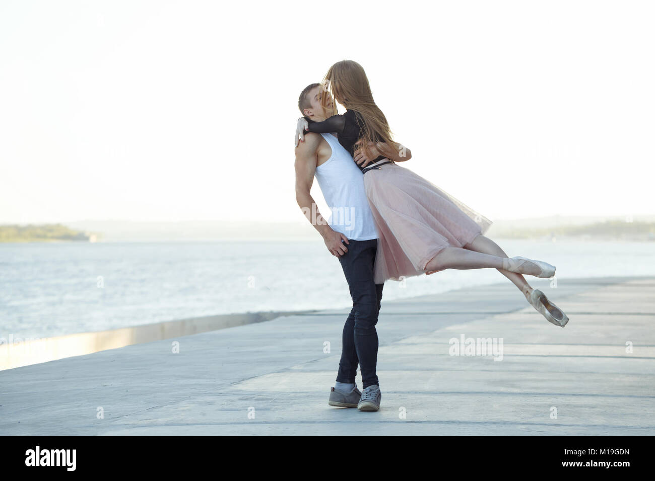 Slender ballerina dances with a modern dancer. Dating lovers. Passion and romance of dance. Performance in the streets - Stock Image
