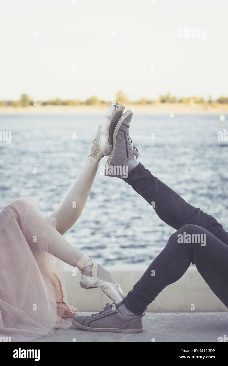 Slender ballerina dances with a modern dancer. Dating lovers. Passion and romance of dance. Legs close-up. He is Stock Photo