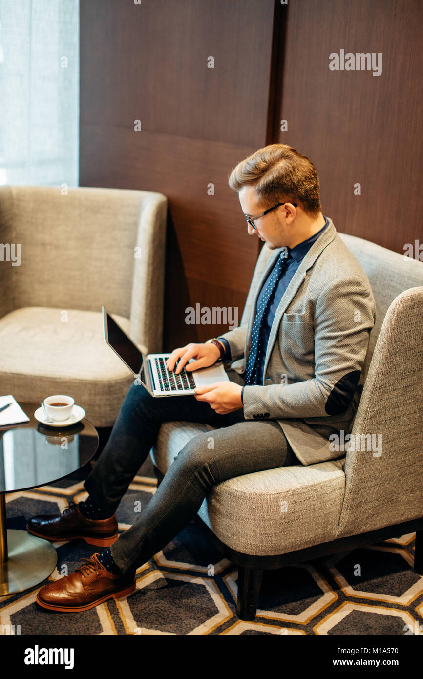 man works on laptop to business done early with cup of coffee - Stock Image