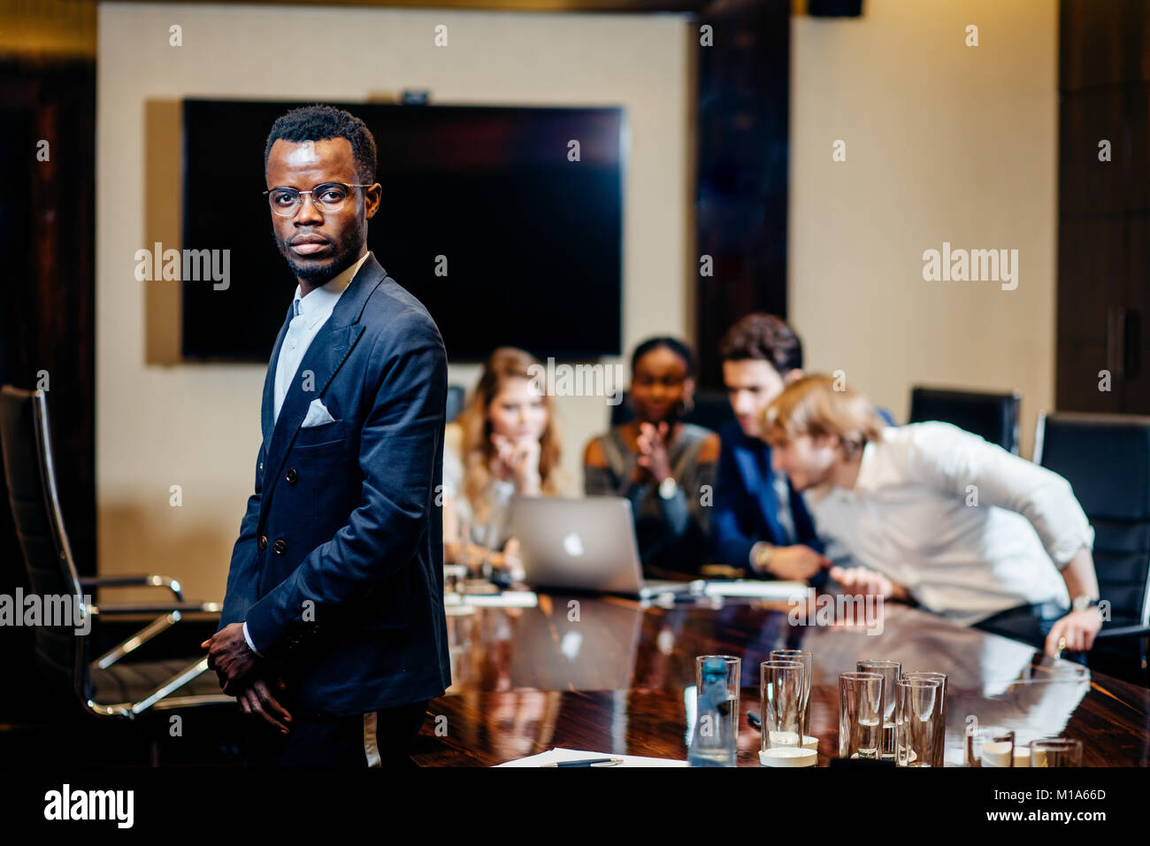 african businessman looking on camera with group of businesspeople on background - Stock Image