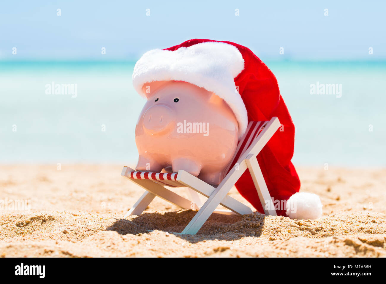 A Pink Piggy Bank With Santa Hat Kept On The Deck Chair At Beach - Stock Image