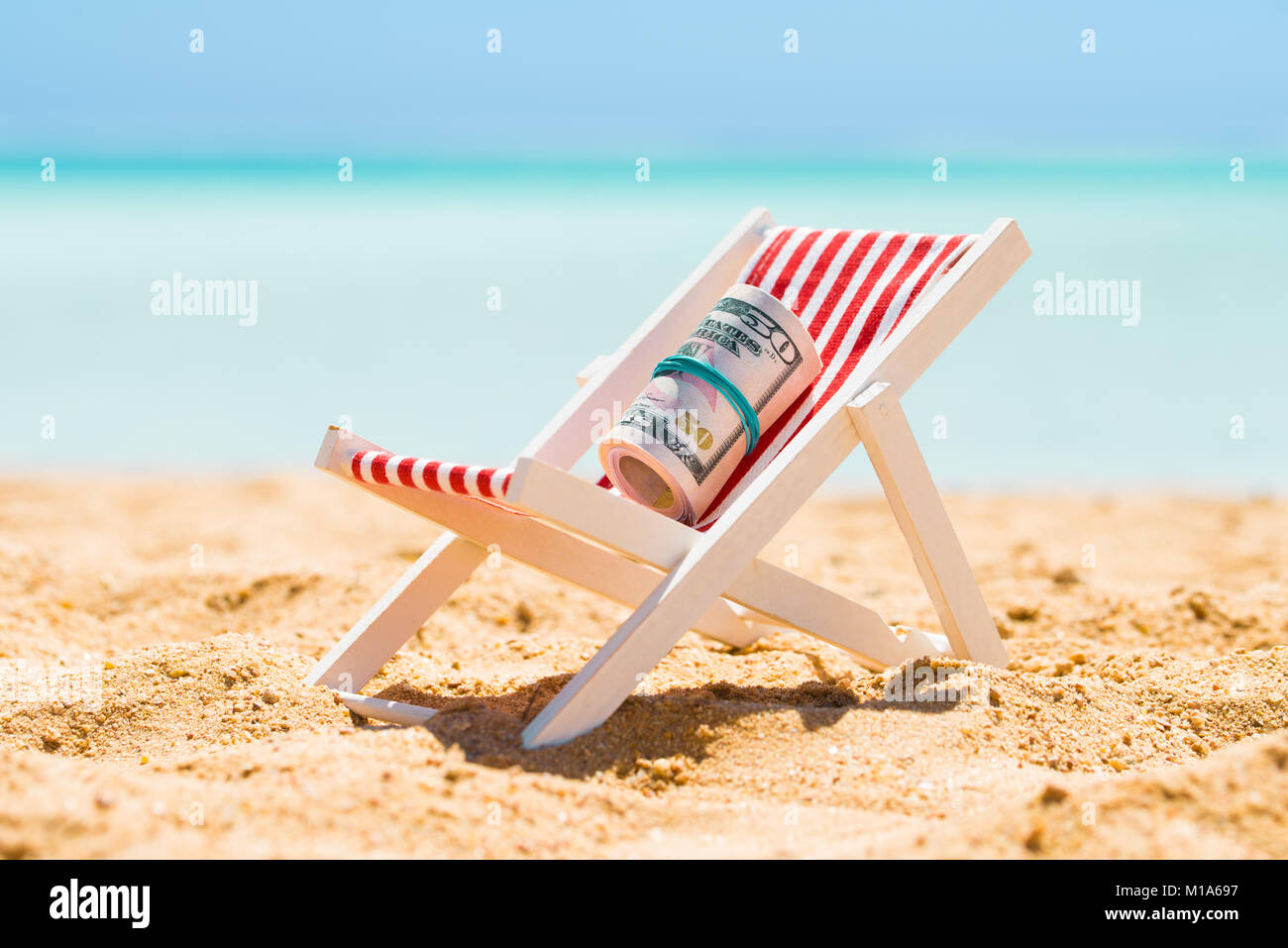 Rolled Up Bundle Of Fifty Dollar Banknotes On Miniature Deck Chair At Beach - Stock Image