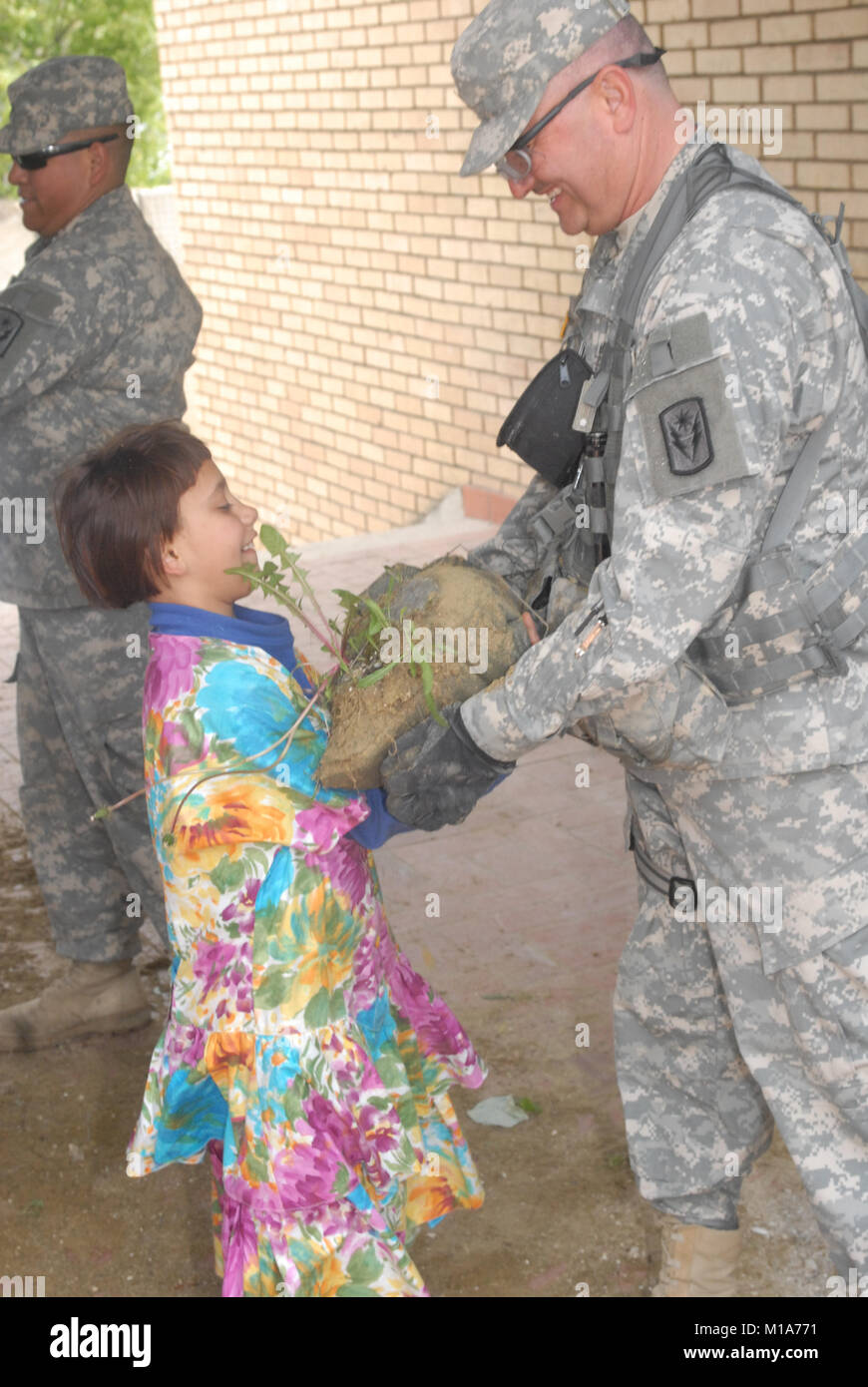 090428-A-7834S-005  A Multi-National Task Force-East Soldier gets help from a local Kamenica/Kamenice girl while - Stock Image