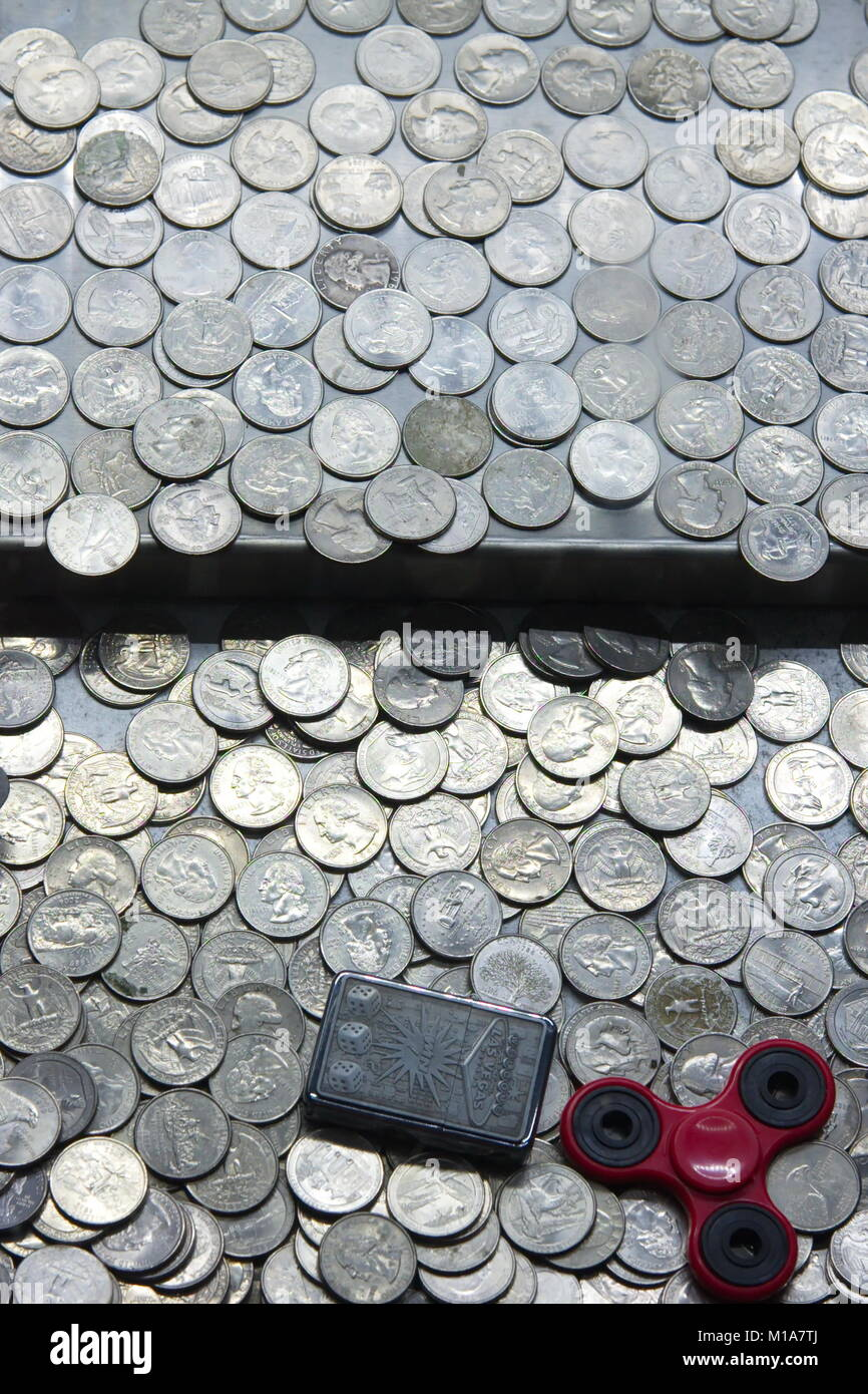 Amusement arcade machine full of United States twenty five cent coins (quarters). a fidget spinner and cigarette - Stock Image