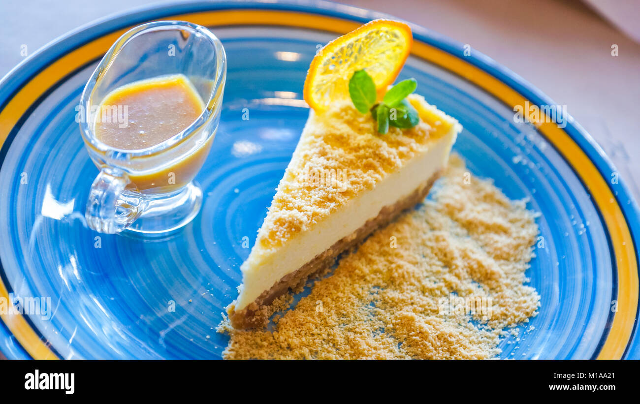 Cheesecake with sea-buckthorn sauce in a blue with yellow stripe plate close up - Stock Image